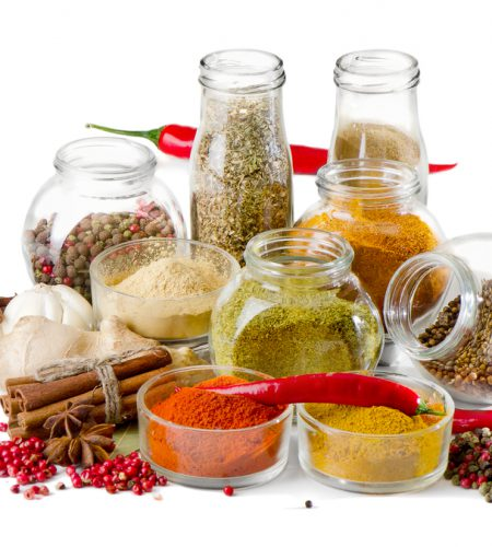 Bottles of colorful spices on white background